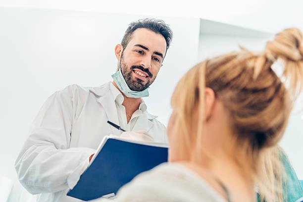 Junge weibliche Patienten in Zahnarzt und er schaut an, Notizen – Foto