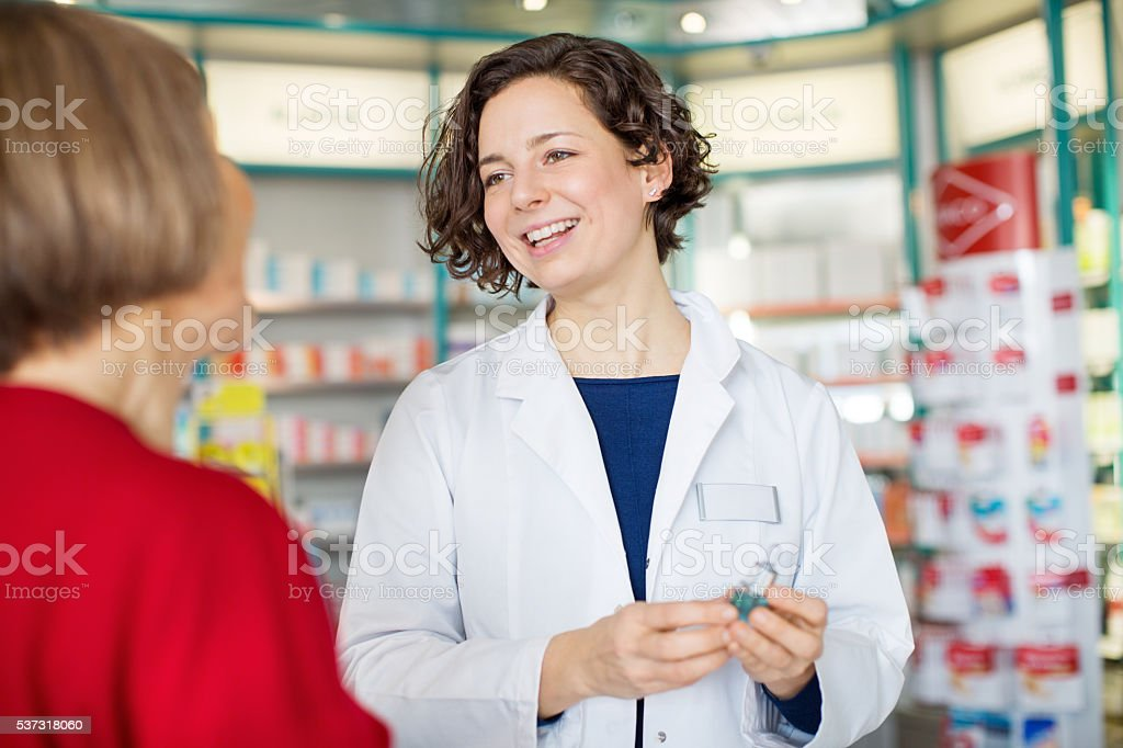 Young female pharmacist assisting customer stock photo