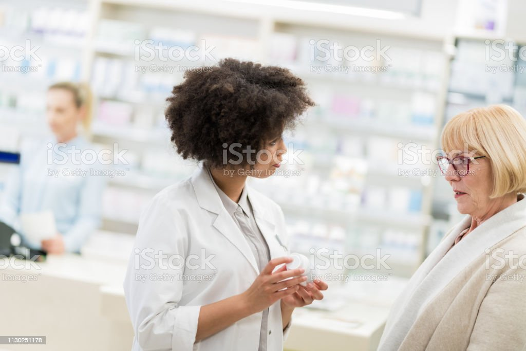 Young Female Pharmacist Giving Advice To Senior Woman
