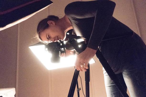 Young Female Photographer Using DSLR Camera in Photo Studio stock photo
