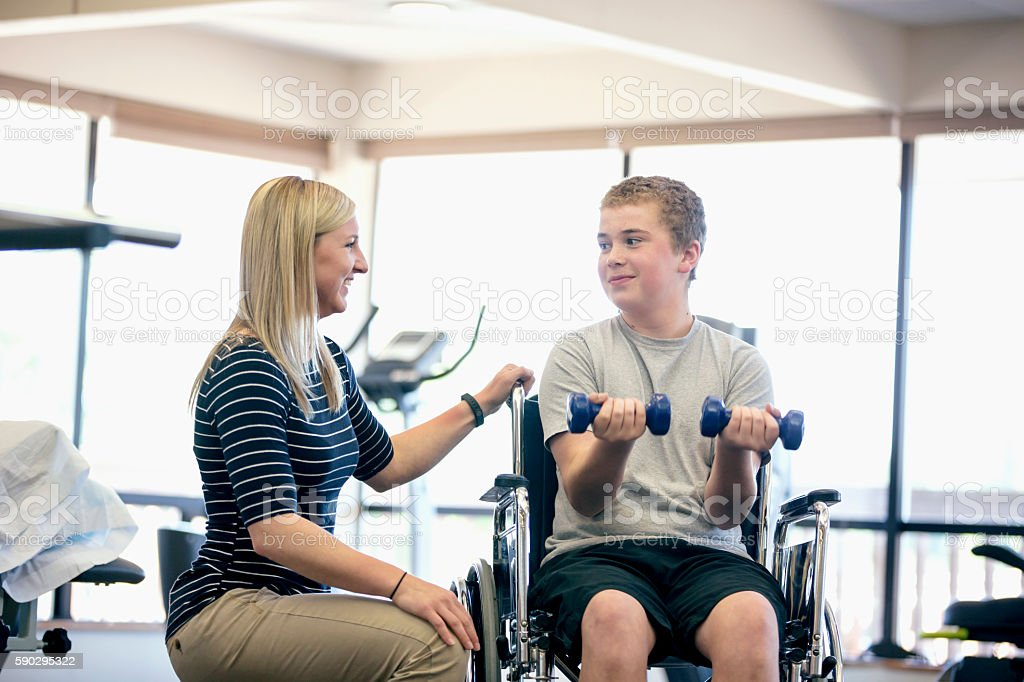 Young female physical therapist encouraging young male patient royaltyfri bildbanksbilder