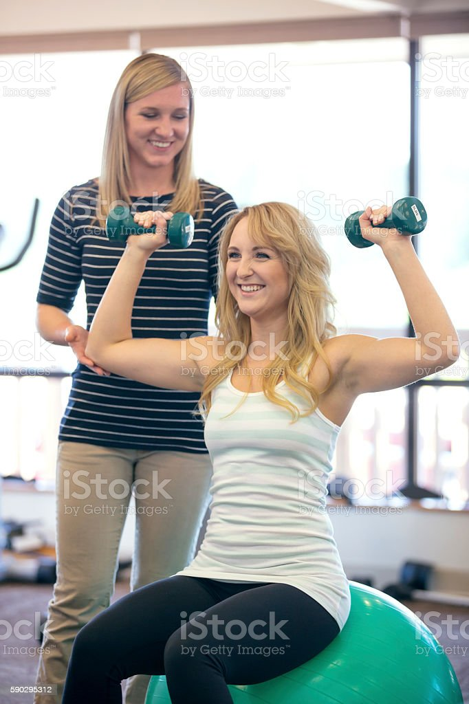 Young female physical therapist helping female patient with an exercise royaltyfri bildbanksbilder