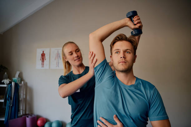 Young female physiotherapist helping patient to raise dumbbells in rehabilitation centre Young physiotherapist helping man exercise with dumbbells sports medicine stock pictures, royalty-free photos & images