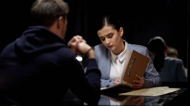 Young female police officer comparing suspect statements with file documents Young female police officer comparing suspect statements with file documents police meeting stock pictures, royalty-free photos & images