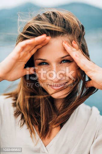 Close up portrait of a young female enjoying summer breeze and looking at the camera