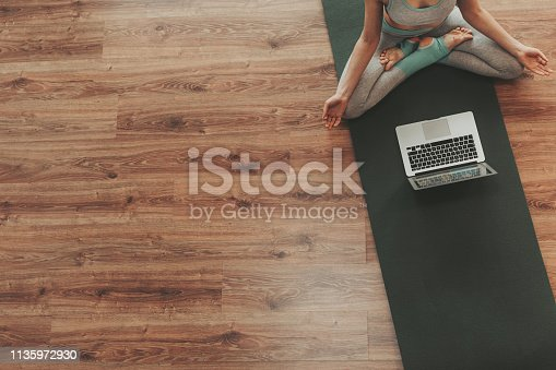 istock Young female practicing padmasana yoga pose alone 1135972930