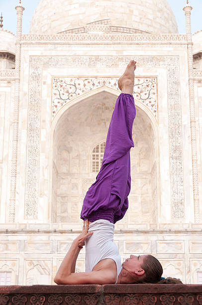 Young female practising yoga asana Sarvangasana at Taj Mahal Young female practising yoga asana Sarvangasana at Taj Mahal, India shoulder stand stock pictures, royalty-free photos & images