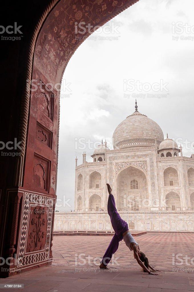 Young female practising yoga pose at Taj Mahal stock photo
