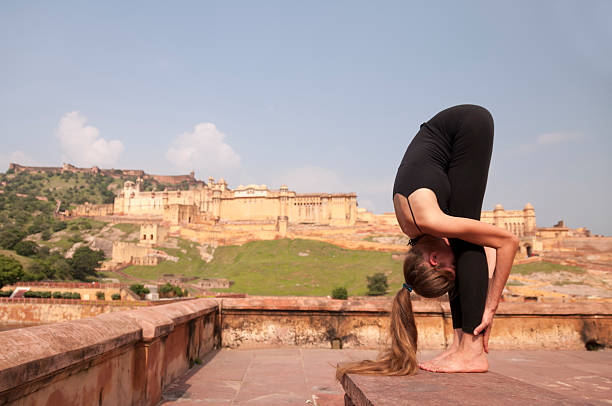 young female practising yoga pose standing forward fold or uttanasana - mahroch stock pictures, royalty-free photos & images