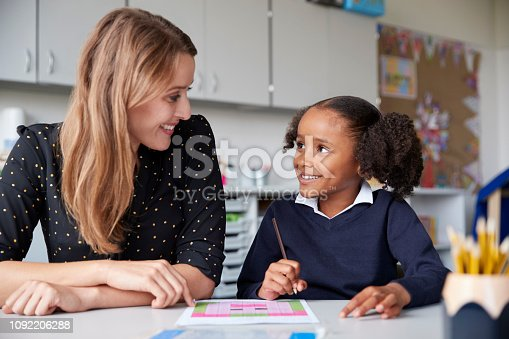 Young female primary school teacher working one on one with a schoolgirl at a table in a classroom, both looking at each other smiling, close up