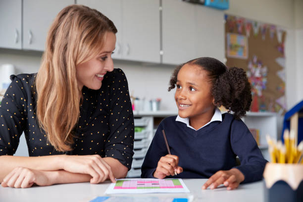 Young female primary school teacher working one on one with a schoolgirl at a table in a classroom, both looking at each other smiling, close up stock photo