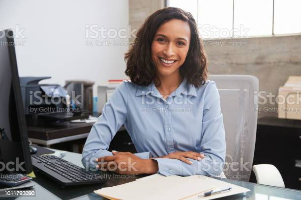 Young female professional at desk smiling to camera picture id1011793090?b=1&k=6&m=1011793090&s=612x612&h=wmbors2y jorkbahrvy1sfxufdvfrhqqfj s2fngxbm=