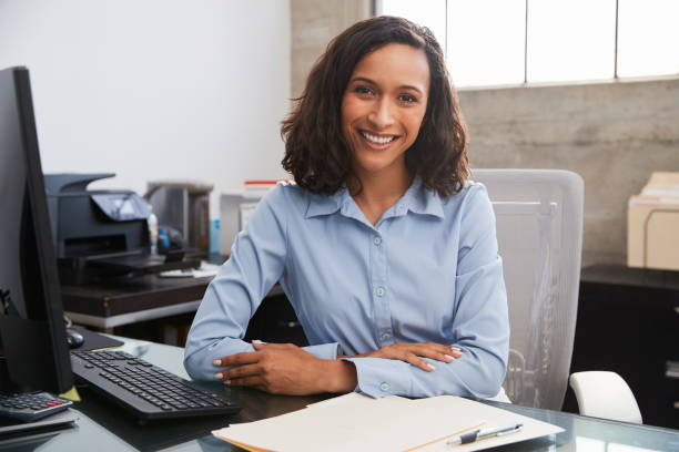young female professional at desk smiling to camera - donna foto e immagini stock