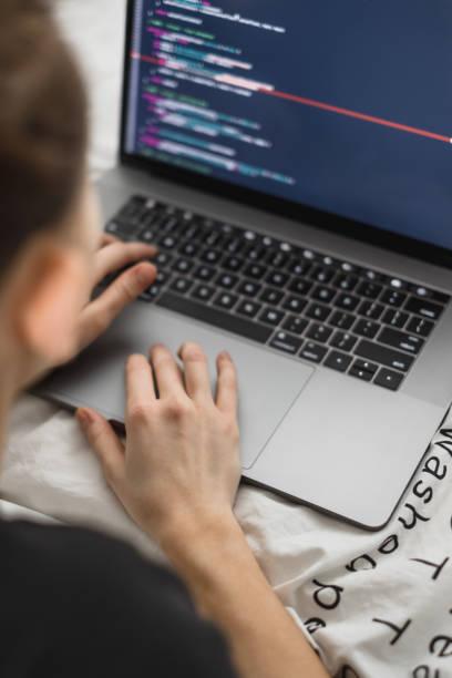 joven programadora femenina escribe el código del programa en un ordenador portátil en la cama. - website design fotografías e imágenes de stock