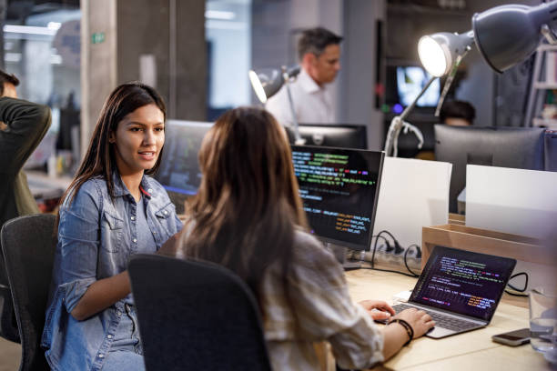 Young female programmers talking in the office. stock photo