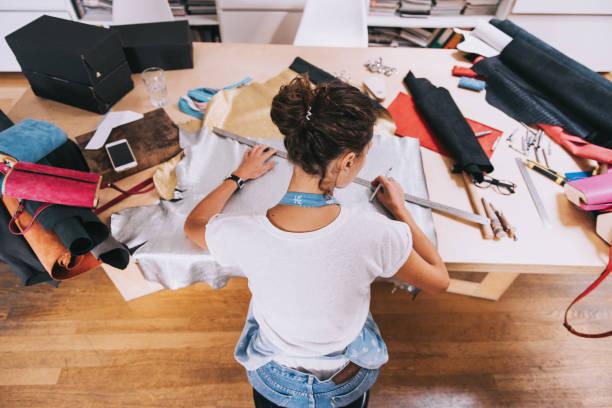 junge weibliche geldbörse-hersteller arbeiten mit ledertextil bei ihrer werkstatt. - diy leder stock-fotos und bilder