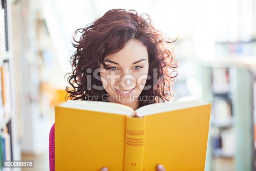 Portrait of young female reading a book at the library