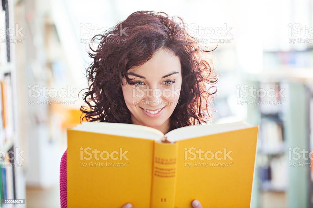 Young female reading a book at the library stock photo