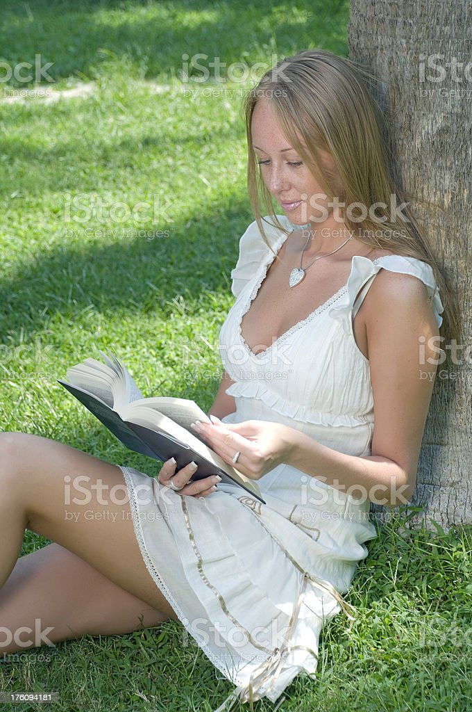 Young female reading book stock photo