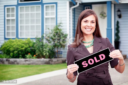 Exterior shot of woman with sold sign.
