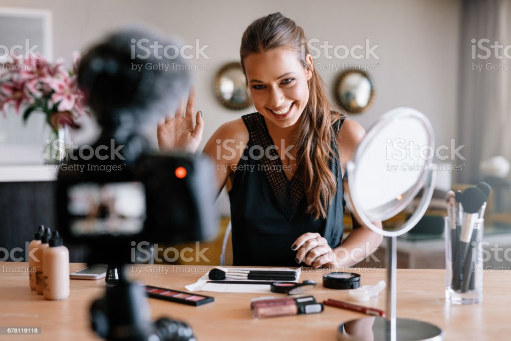 Young female recording video for her blog on the theme of beauty and fashion. stock photo
