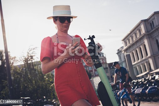 874772840istockphoto Young female rented en electric scooter. 1165096417