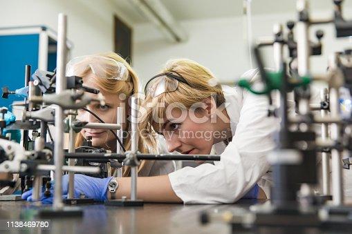 Young Female Researcher Assembling Laser Experimentation Platform.