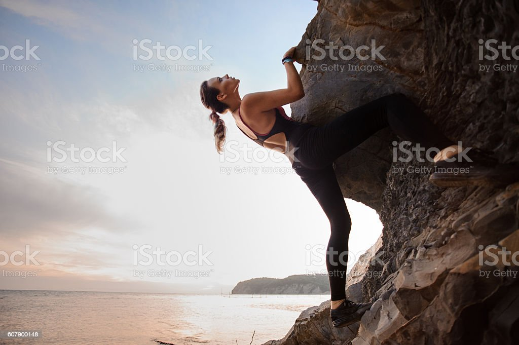 Young female rock climber climbing challenging route on overhanging cliff stock photo