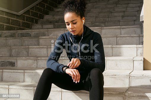 Young female runner checking her pulse with an activity tracker after training