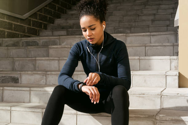 Young female runner checking her pulse Young female runner checking her pulse with an activity tracker after training fitness tracker stock pictures, royalty-free photos & images