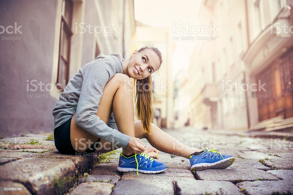 Young female runner tying her shoes stock photo