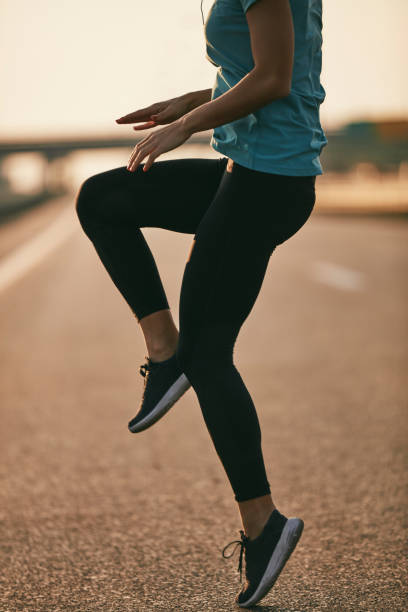 Young female runner warming up before jogging