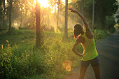 istock Young female runner warming up before running at morning forest trail 696178526