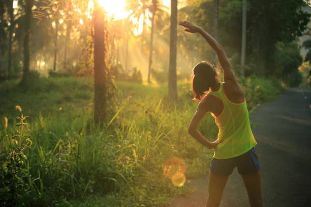 junge weibliche läufer aufwärmen vor laufen am morgen waldweg - joggerin stock-fotos und bilder