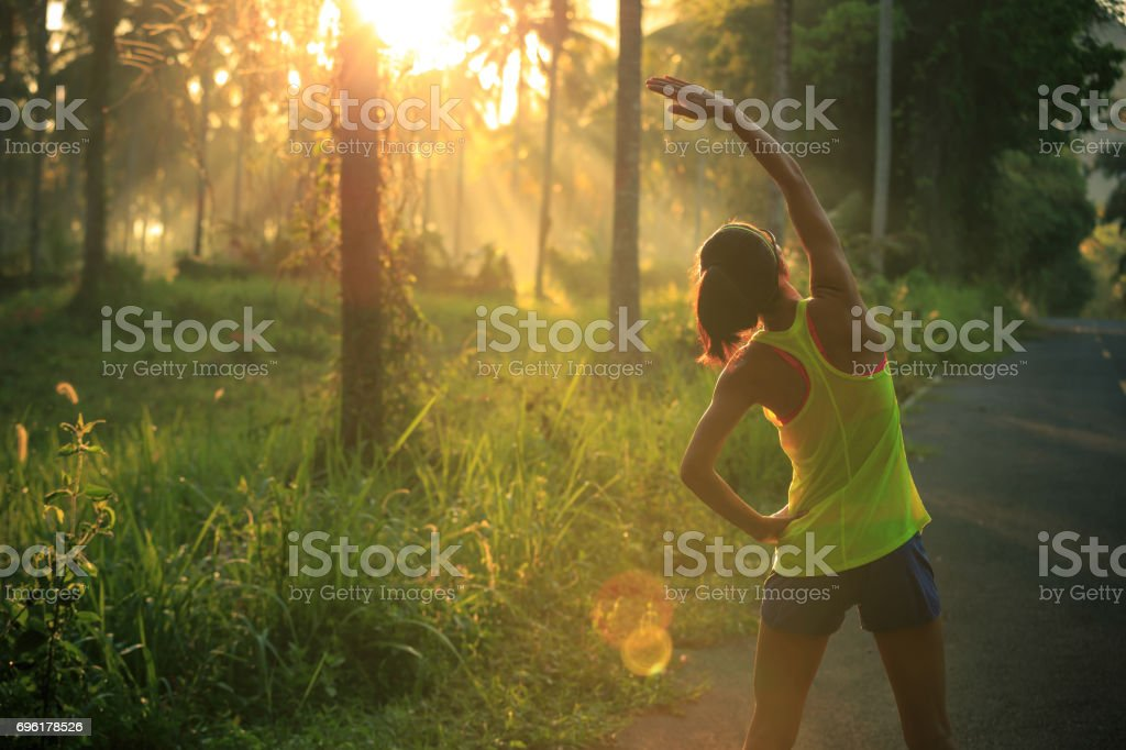 Young female runner warming up before running at morning forest trail stock photo