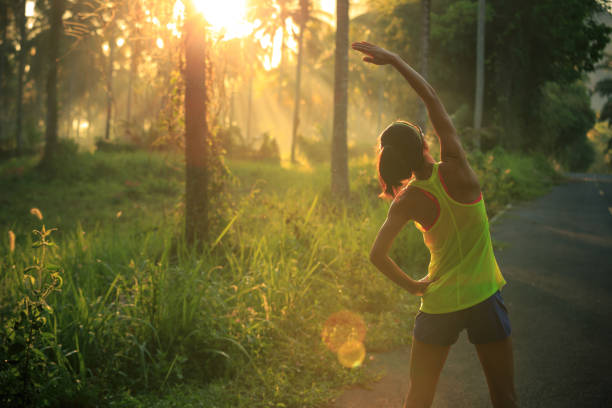 young female runner warming up before running at morning forest trail - jogging stock pictures, royalty-free photos & images