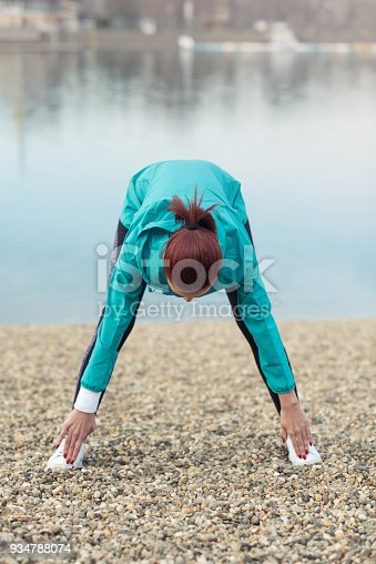638628530 istock photo Young female runner warming up before running at the beach 934788074