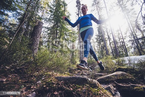 Beautiful female jogging in forest.