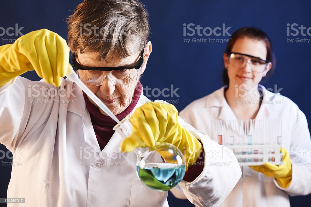 Young female scientist smilingly watches older colleague working in lab royalty-free stock photo