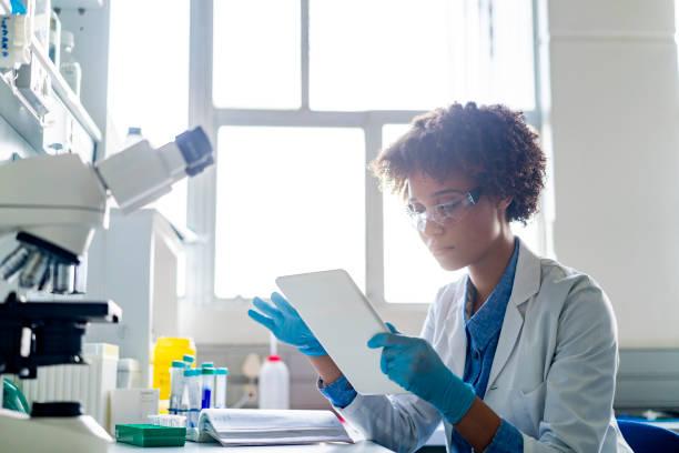 Junge Wissenschaftlerin mit digital-Tablette im Labor – Foto
