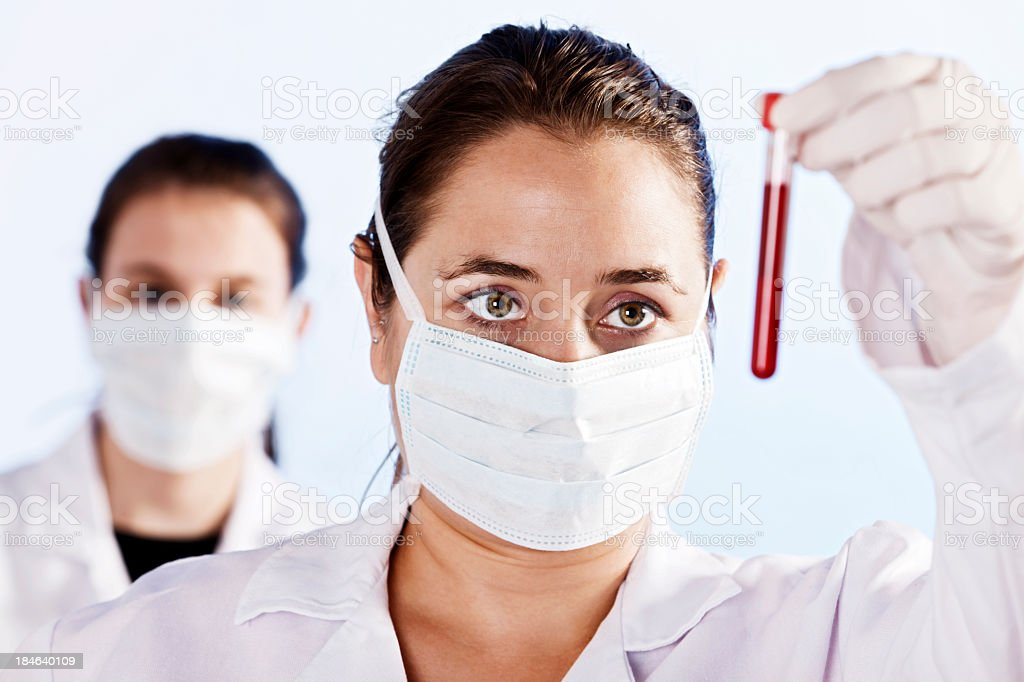 Young female scientists examine vial of blood in laboratory royalty-free stock photo