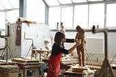 istock Young Female Sculptor is working in her studio 960077510