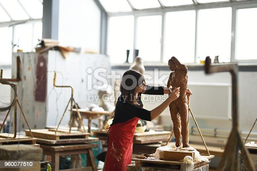 istock Young Female Sculptor is working in her studio 960077510