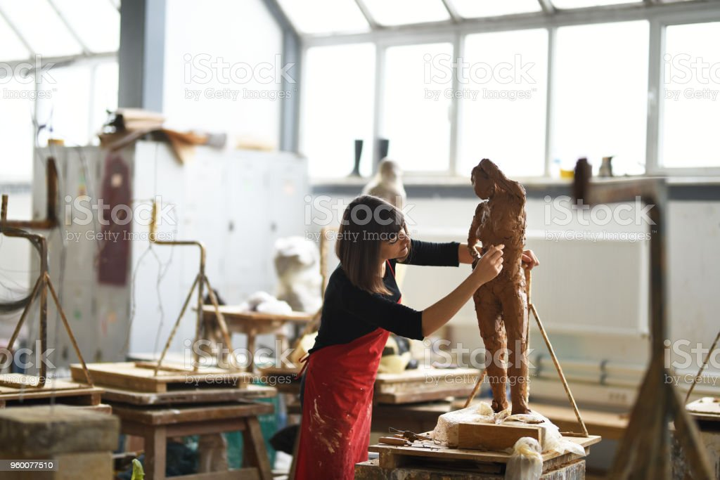 Young Female Sculptor is working in her studio stock photo