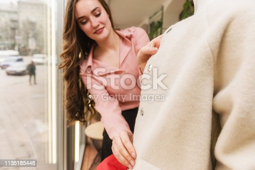 672064598istockphoto Young female seller dressing up a mannequin 1135185448