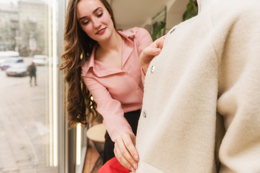 672064598 istock photo Young female seller dressing up a mannequin 1135185448