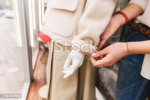672064598istockphoto Young female seller put beige coat on mannequin. 1134757655