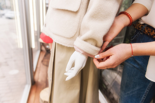 672064598 istock photo Young female seller put beige coat on mannequin. 1134757655