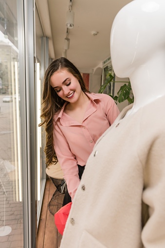 672064598 istock photo Young female seller put beige coat on mannequin. 1135185433