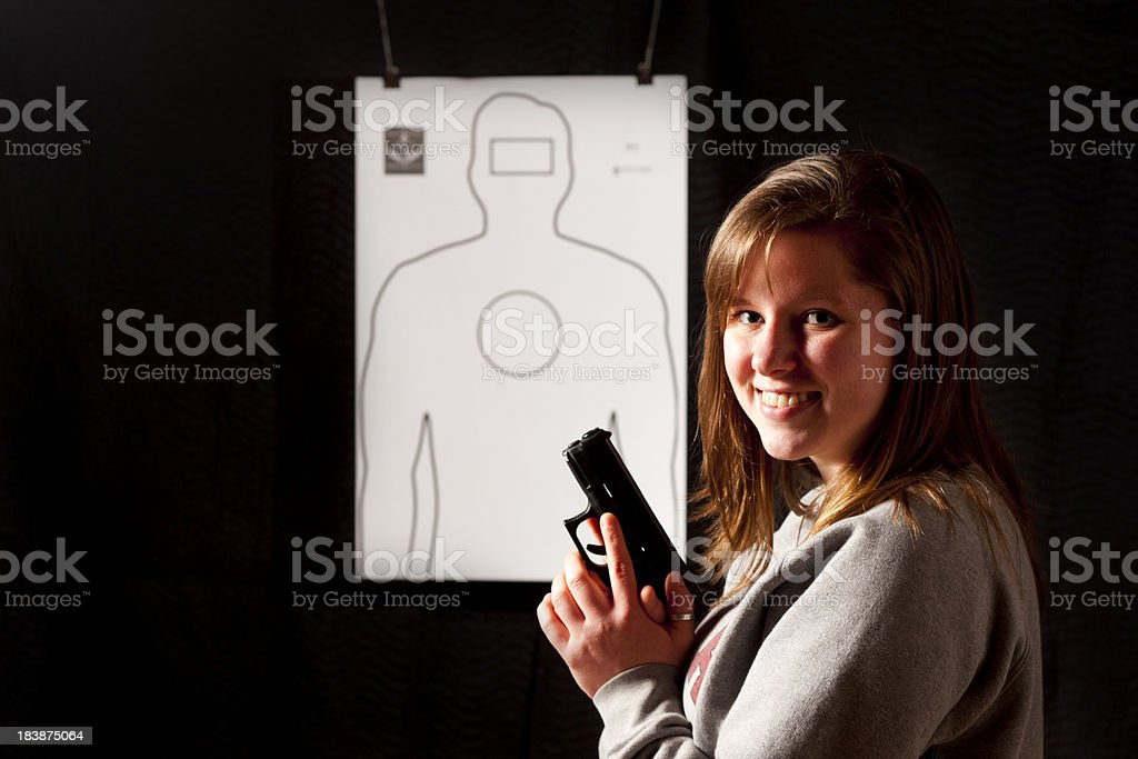 \'A young woman smiling. Holding a modern polymer, semiautomatic,...